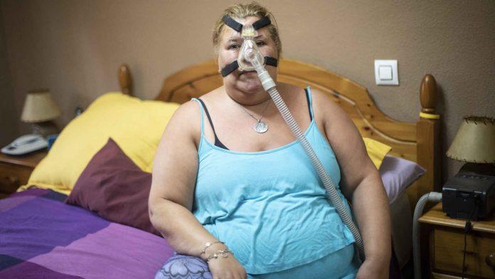 Arancha (44) posa con el respirador que necesita para dormir cada noche. Jorge Barreno
