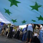Un grupo de personas extienden una bandera con las siete estrellas verdes durante una concentración