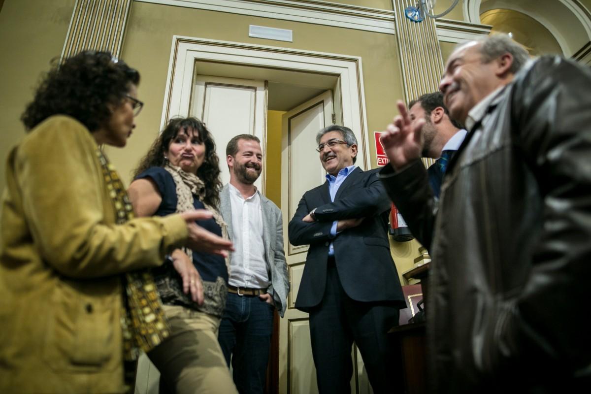 El portavoz de NC, Román Rodríguez, charla con integrantes del Grupo de Podemos, en el  salón de sesiones del Parlamento   FOTO: Andrés Gutiérrez