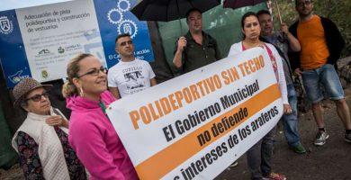 Miembros del colectivo, ayer con pancartas y paraguas a las afueras del polideportivo / A. GUTIÉRREZ