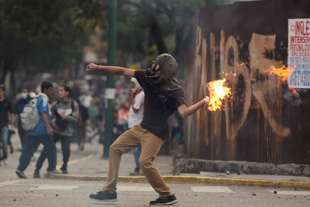 A demonstrator throws a molotov cocktail during clashes with riot police while rallying against Venezuela's President Nicolas Maduro in Caracas