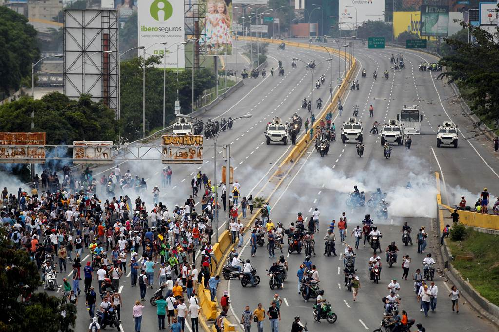 Demonstrators run away from tear gas during clashes with police while rallying against Venezuela's President Nicolas Maduro in Caracas
