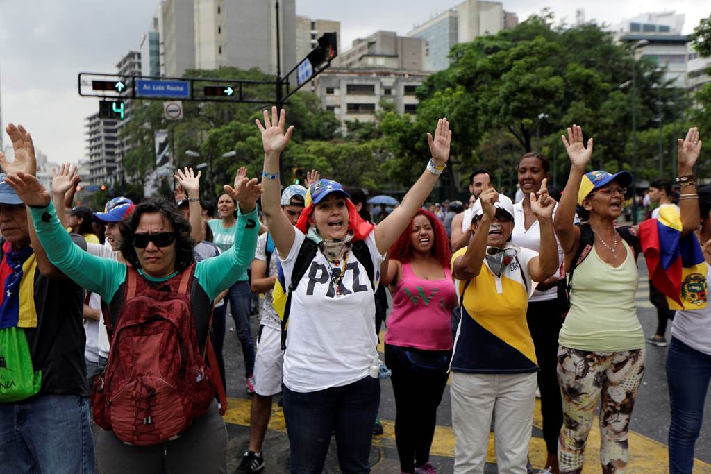 Demonstrators raise their arms during clashes with police while rallying against Venezuela's President Maduro in Caracas