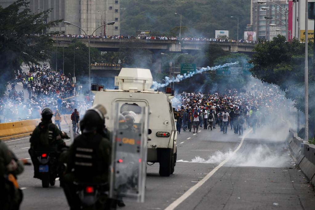 Police fire tear gas toward opposition supporters during clashes while rallying against Venezuela's President Nicolas Maduro in Caracas