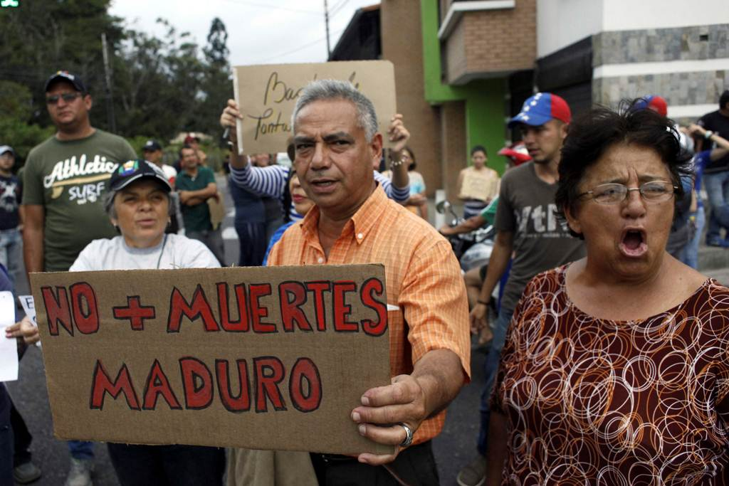 "People holding a placard that reads ""No more deaths, Maduro"" gather outside the wake of Paola Ramirez, a student who died during a protest, in San Cristobal"