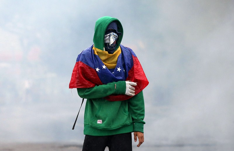 A demonstrator clashes with riot police while rallying against Venezuela's President Nicolas Maduro in Caracas