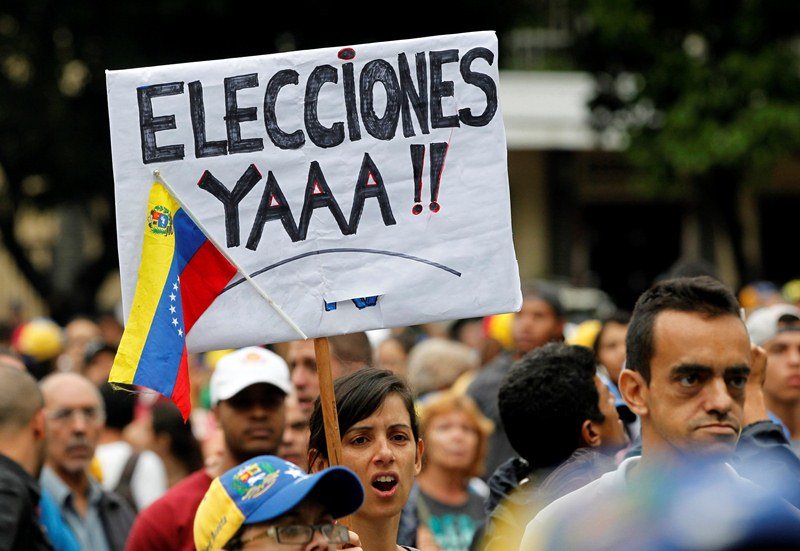 "A demonstrator carries a sign that that reads ""Elections right now"" during a rally against Venezuela's President Nicolas Maduro in Caracas"