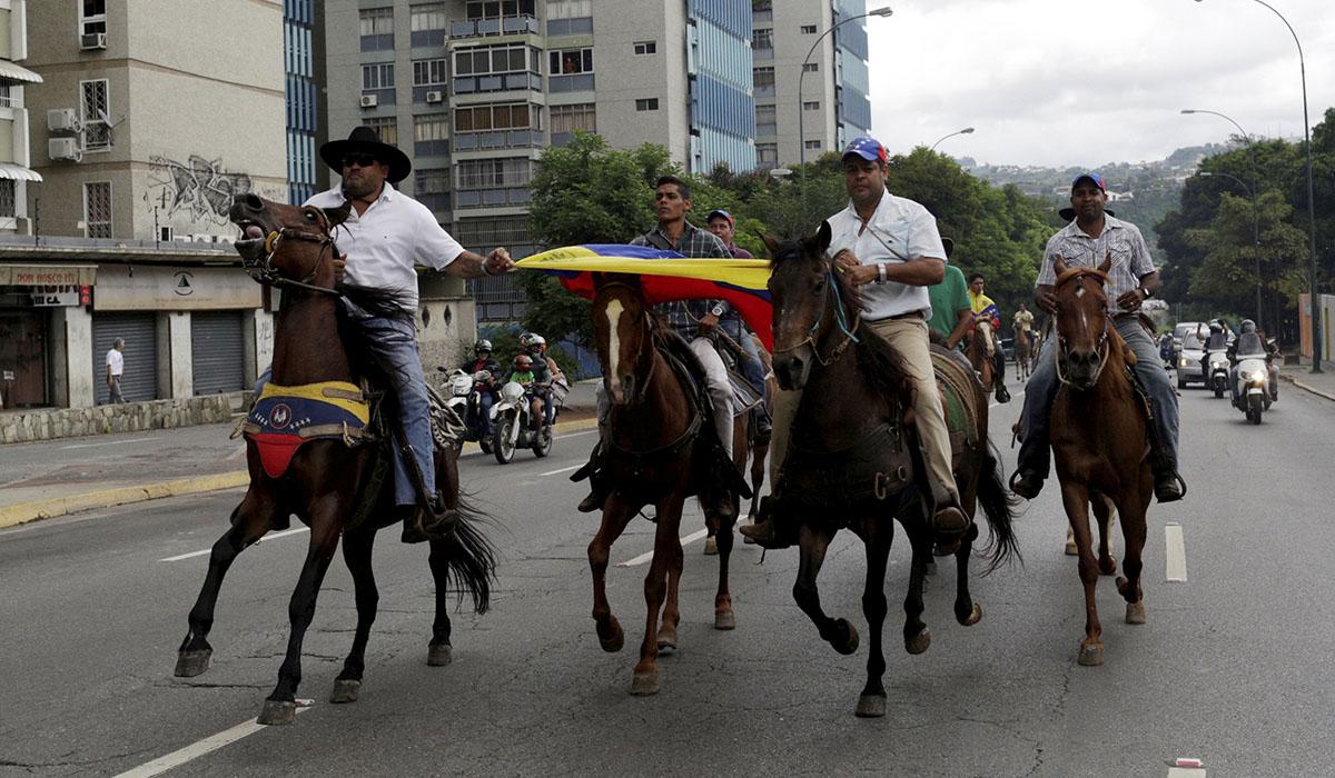 Opositores protestan a caballo en Venezuela. REUTERS/Marco Bello