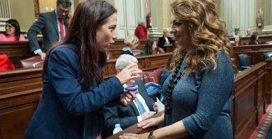 Cristina Valido (derecha), habla con su antecesora al frente de la Consejería de Empleo, Políticas Sociales y Vivienda, Patricia Hernández, en el Parlamento. Andrés Gutiérrez