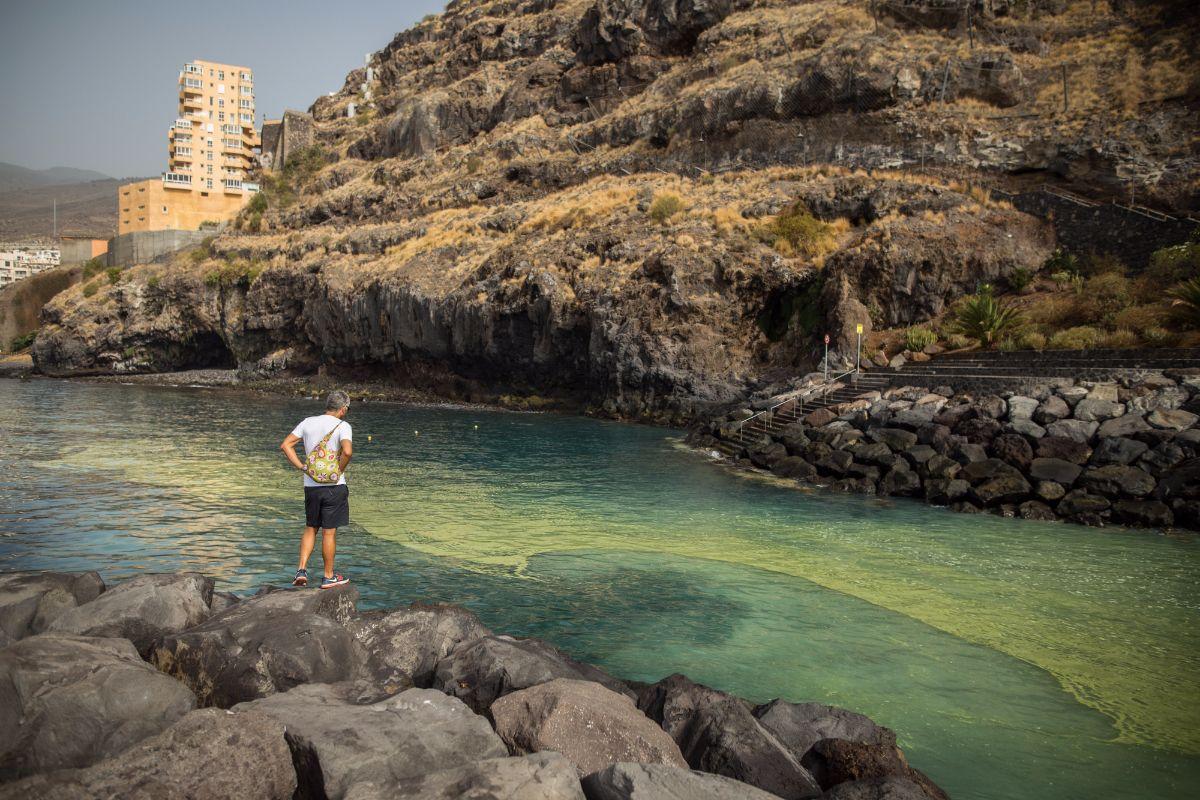 Unos bañistas, ayer, en Radazul, con las manchas de cianobacterias frente a ellos. Andrés Gutiérrez