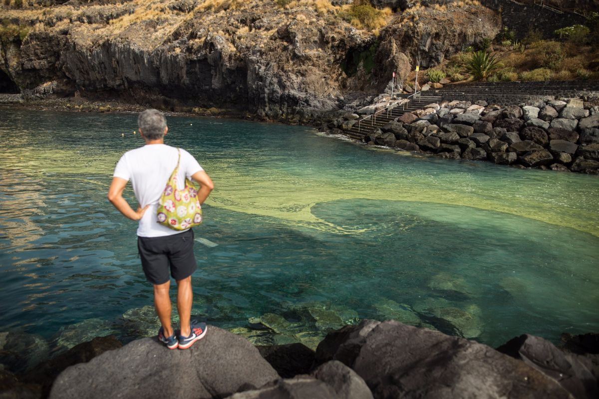 Unos bañistas, ayer, sentados en Radazul, con las manchas de cianobacterias frente a ellos. Andrés Gutiérrez