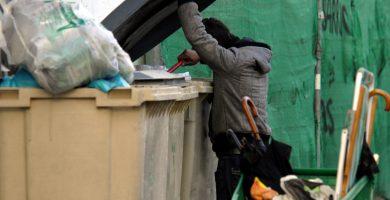 Una persona sin techo rebusca en un contenedor de basura en Tenerife. / DA