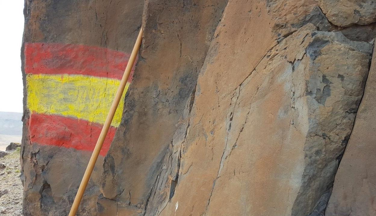 Bandera pintada sobre los grabados rupestres. / TWITTER