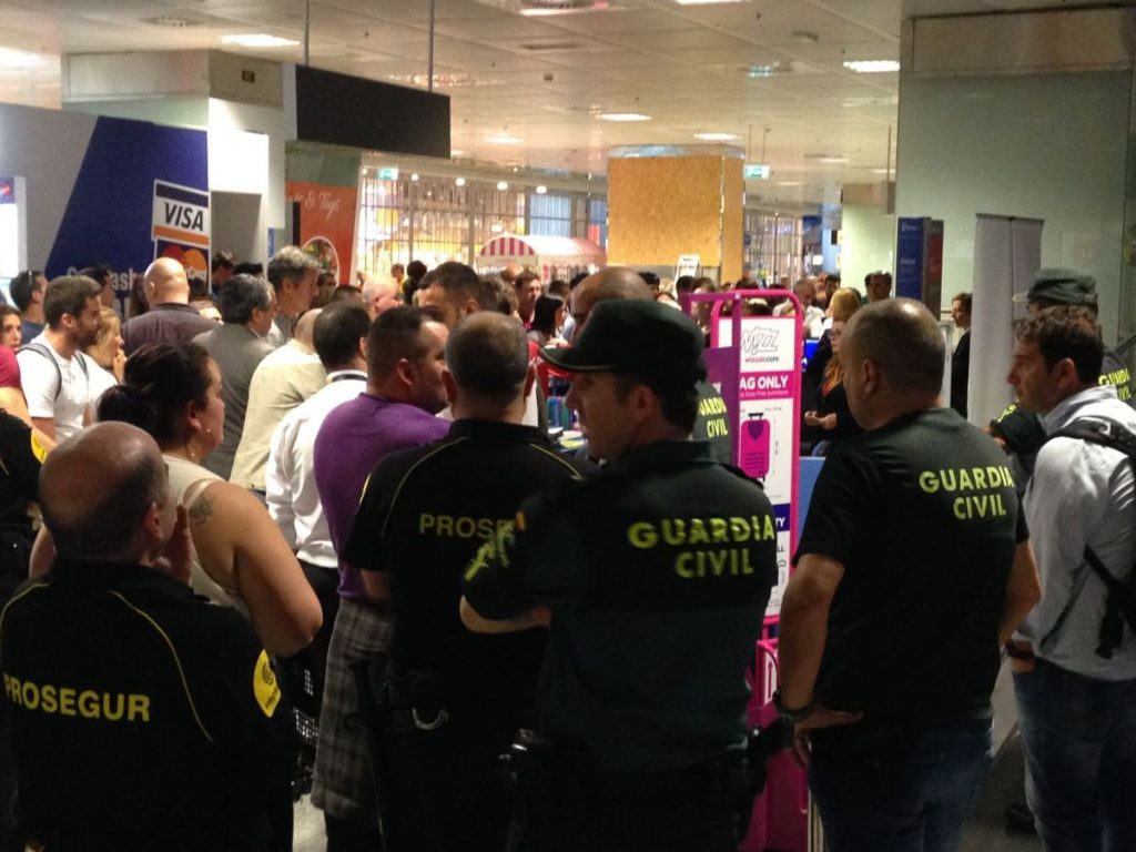 Guardia Civil y vigilantes de seguridad, junto a los irritados pasajeros, ayer en el Reina Sofía. DA