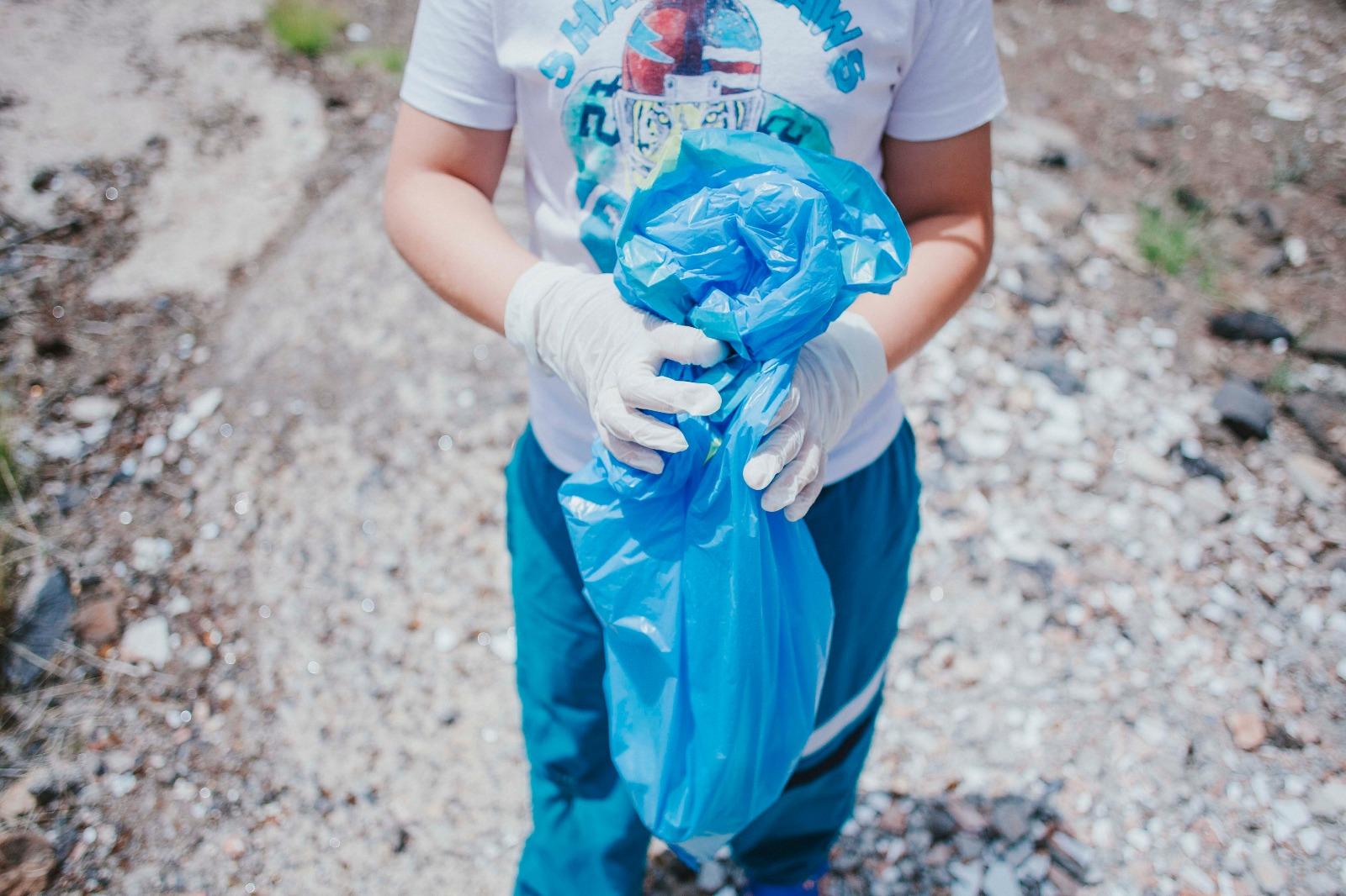 Uno de los alumnos, con basura recogida en la zona. / ziREjA