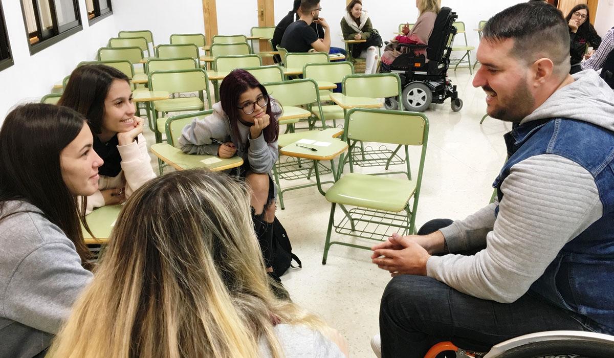 Varias alumnas conversan con un voluntario con discapacidad en un aula. DA