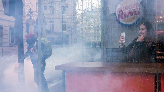 La testigo sonriente desde un 'burger': la foto viral de las protestas en Francia
