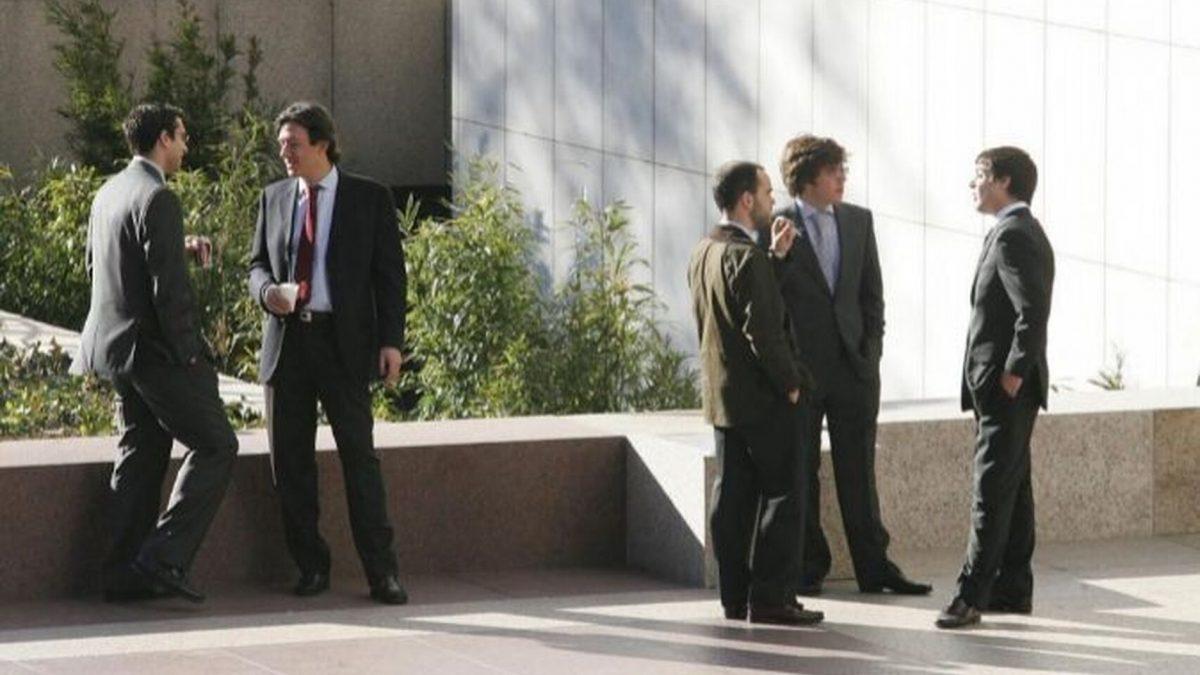 Trabajadores fumando y tomando café en la puerta de una empresa. El Español
