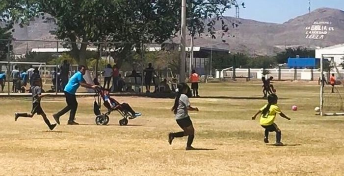 Un padre empuja la silla de ruedas de su hijo para que pueda jugar a fútbol