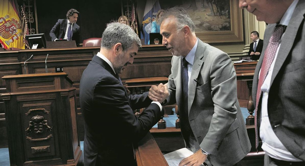 Fernando Clavijo (CC) y Ángel Víctor Torres (PSOE) se saludan ayer en el Parlamento regional al final de la primera sesión para la investidura del nuevo presidente. Foto: Fran Pallero