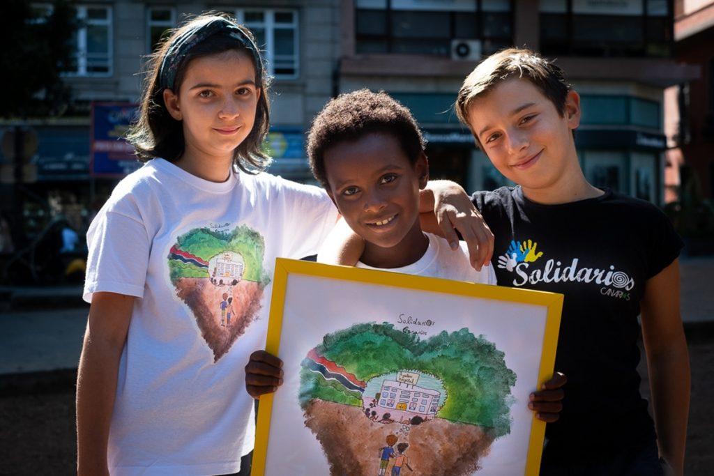 Adriana, Ayalew y Airam posan con el dibujo con el que Solidarios Canarios recauda dinero para su nuevo proyecto en tierras gambianas. Fran Pallero