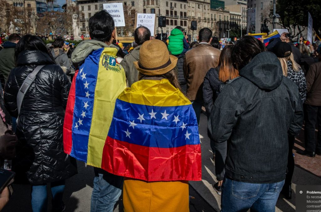 Participantes en la manifestación en Barcelona para respaldar el apoyo de la Unión Europea a Venezuela y el reconocimiento a Juan Guaidó como presidente interino visten banderas venezolanas. EP