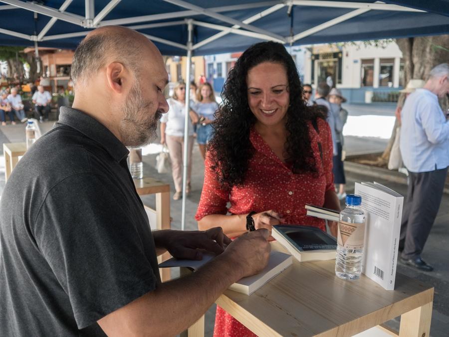 Imagen de la firma de libros con uno de los autores, Nicolás Melini, en la Plaza de España de Los Llanos de Aridane. | JUANCHO GARCÍA