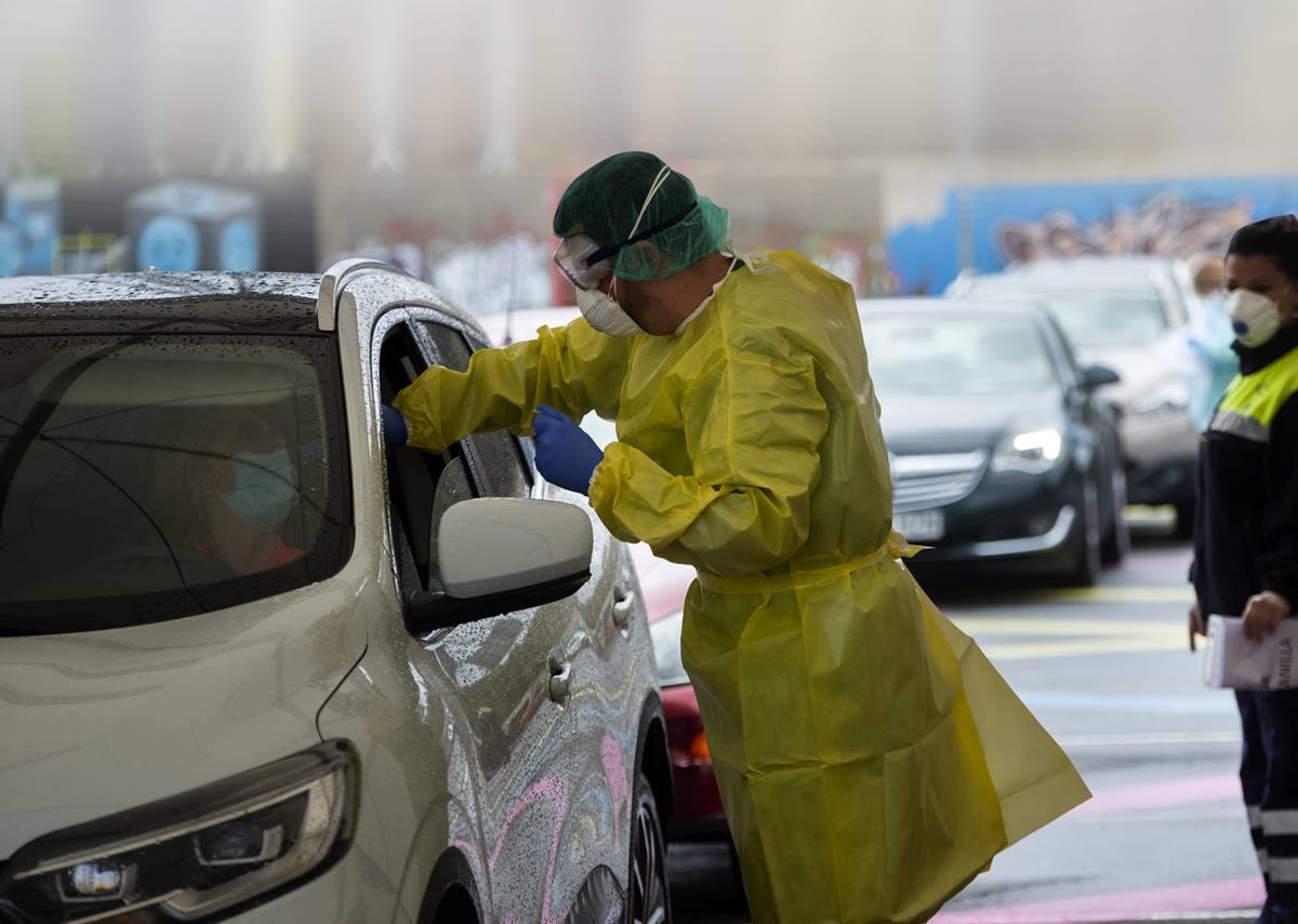 Un miembro del equipo sanitario realiza una prueba a la conductora de un vehículo en el parking de la Facultad de Bellas Artes; El Archipiélago suma ya 287 contagios.