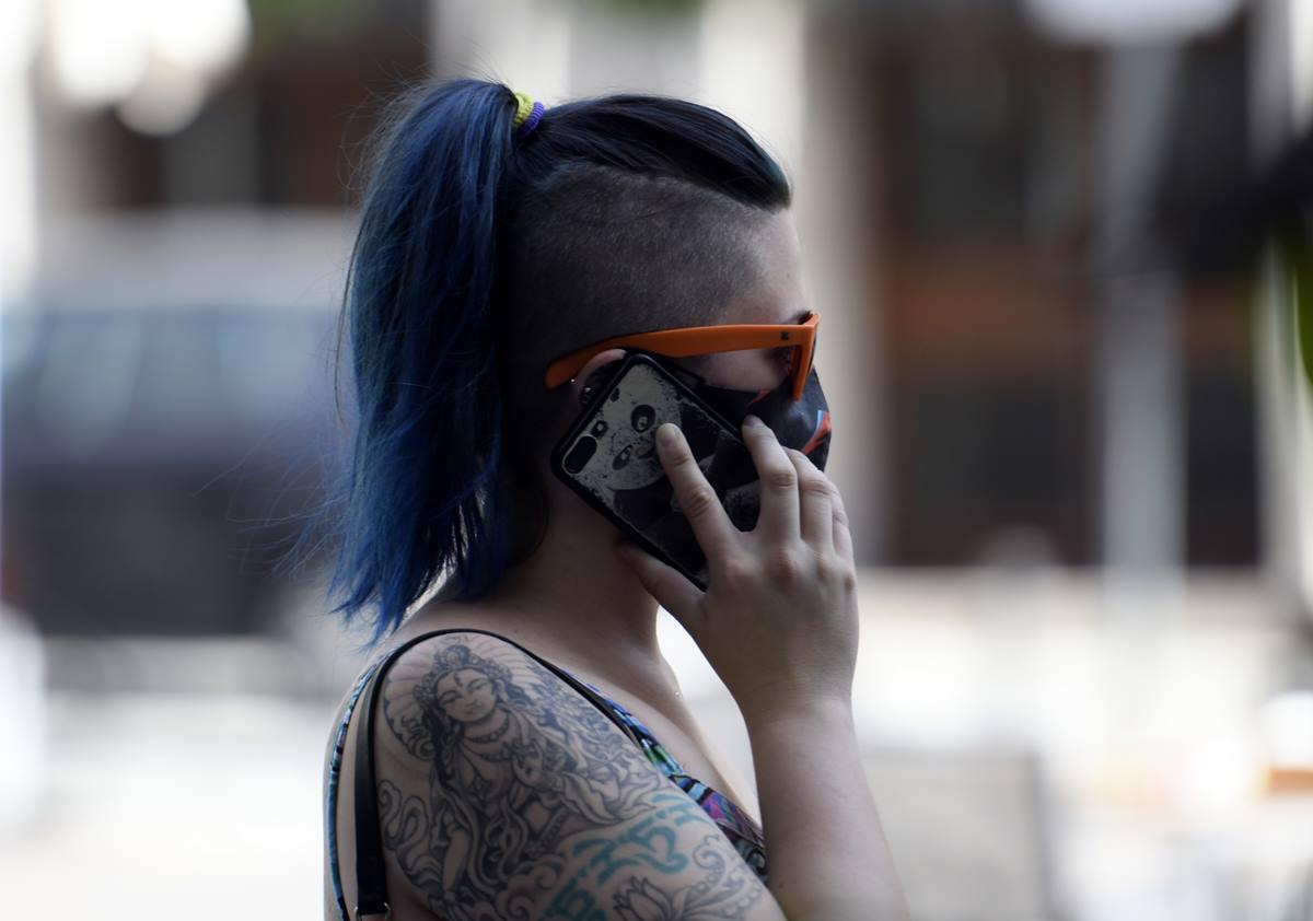 Una mujer con mascarilla habla por teléfono el día en el que entra en vigor en la Comunidad de Madrid