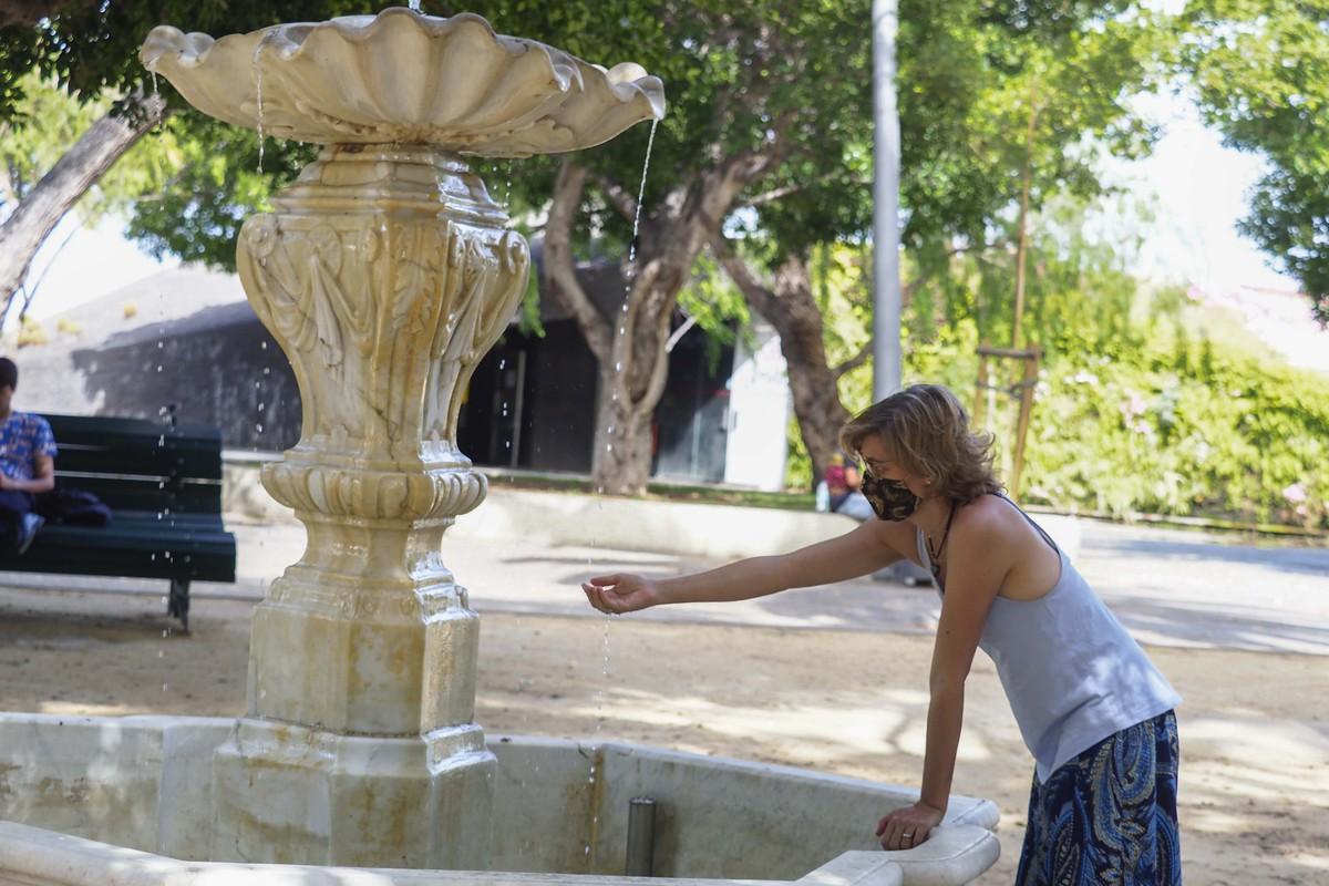 Una mujer se refresca en una fuente de Santa Cruz de Tenerife