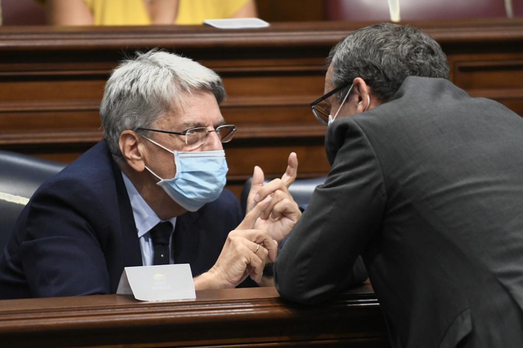 El consejero de Administraciones Públicas, Justicia y Seguridad, Julio Pérez, charla con otro diputado. Rafa Avero (Parlamento)
