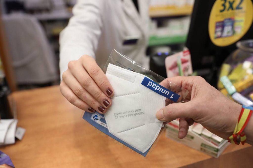 Una anciana recoge una mascarilla FFP2 en la farmacia. Imagen de recurso de EP